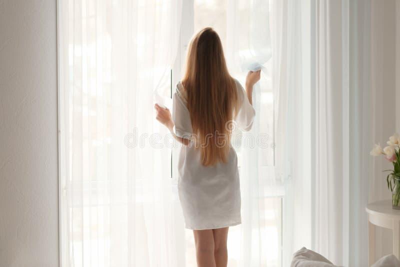 Cortinas de abertura de la mujer joven en casa imagenes de archivo