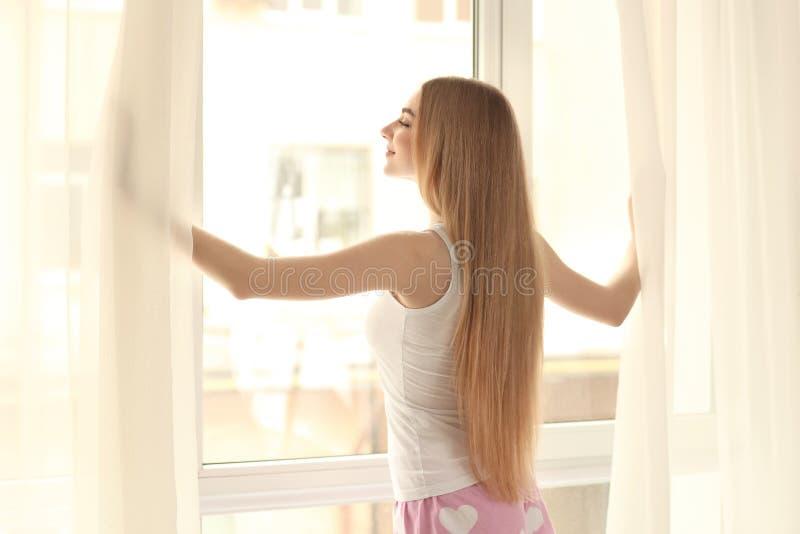 Cortinas de abertura de la mujer joven en casa fotografía de archivo libre de regalías