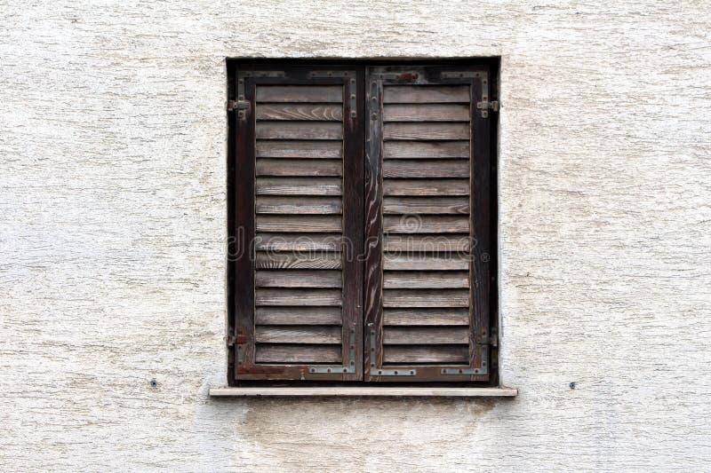 Cortinas de janela de madeira dilapidadas Closed com cor desvanecida e as dobradiças oxidadas do metal montadas na parede suja da fotografia de stock