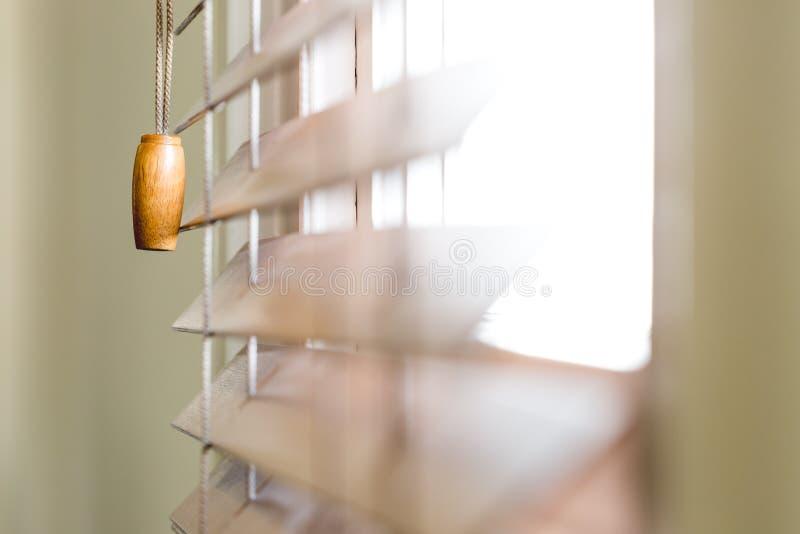 Cortinas de janela de madeira parcialmente fechados com luz brilhante imagens de stock