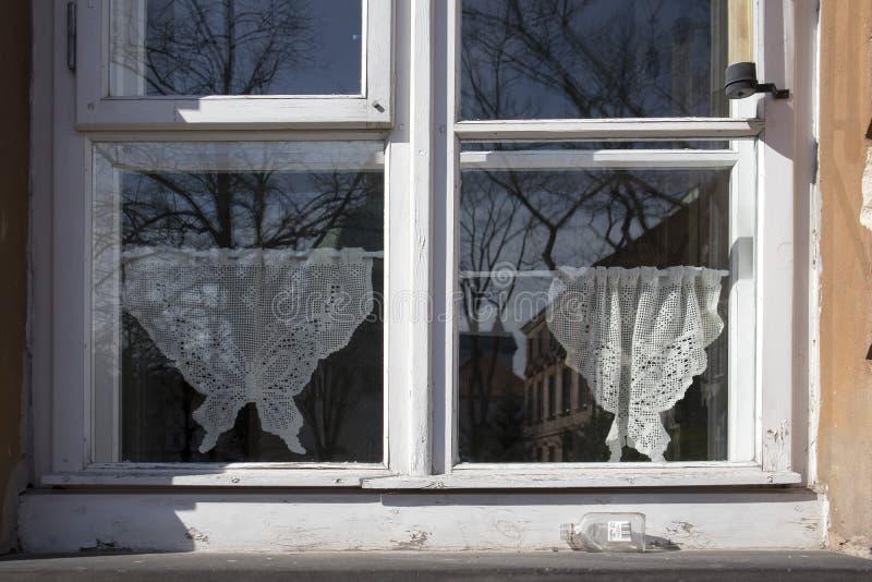 Cortinas de Tulle en la ventana vieja en Varsovia fotos de archivo