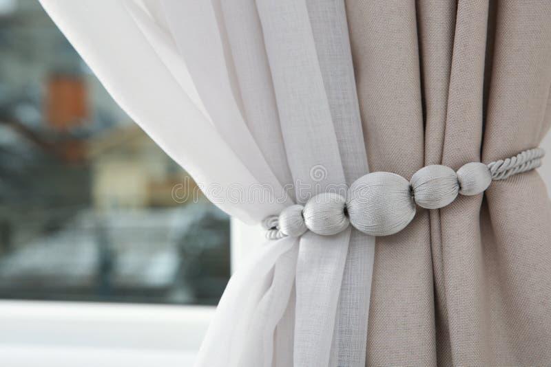 Cortinas de ventana cubiertas con el tieback en sitio imagen de archivo