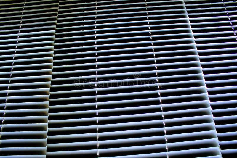 Cortinas horizontais de alumínio brancas em Windows fechado imagens de stock