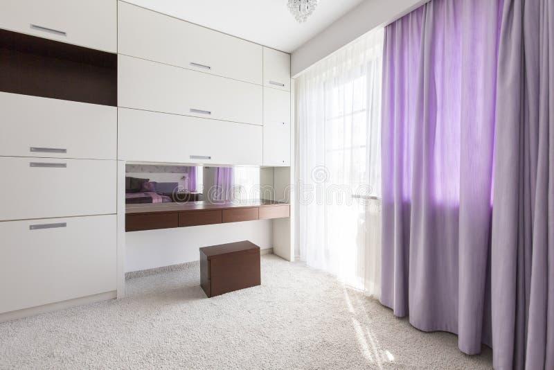 Cortinas púrpuras en el dormitorio fotografía de archivo