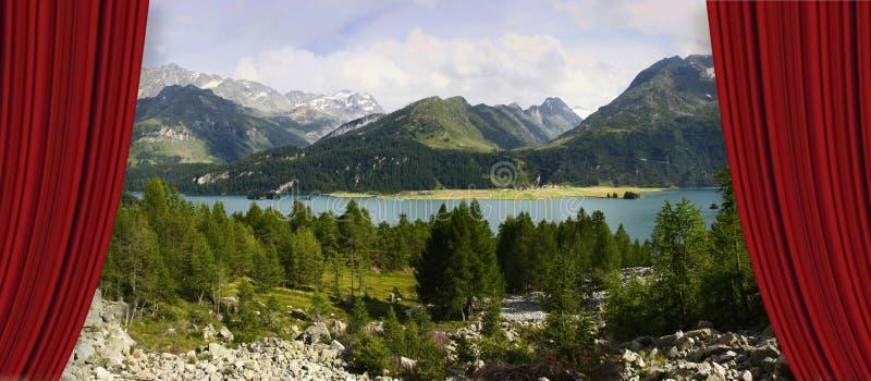Cortinas rojas del teatro abierto contra el lago sils en el valle superior de Engadine en un día de verano Europa - Suiza - image fotos de archivo