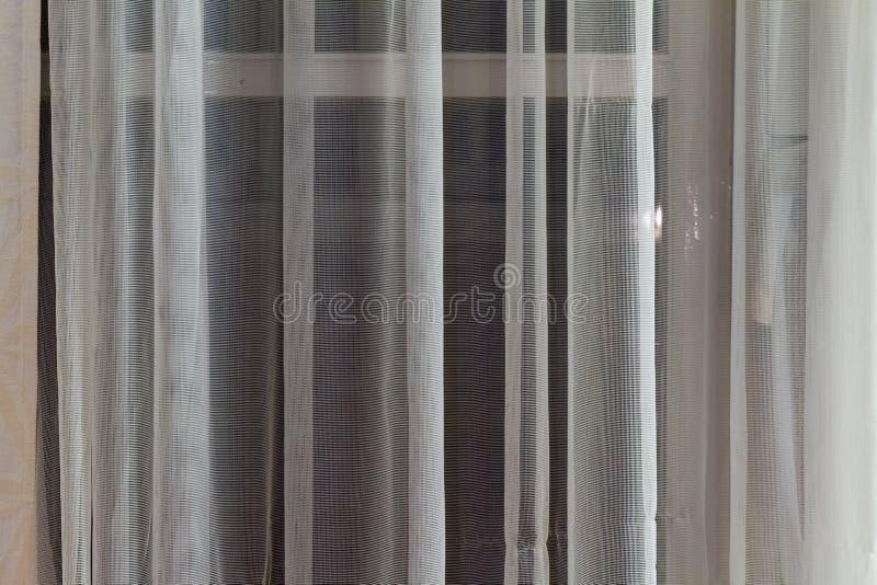 Cortinas translúcidas finas que cuelgan en una ventana fotos de archivo