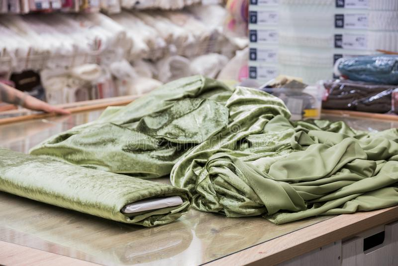 Cortinas verdes del terciopelo en un rollo en la tabla para medir el corte en tiendas Muestras de textura de telas multicoloras foto de archivo libre de regalías