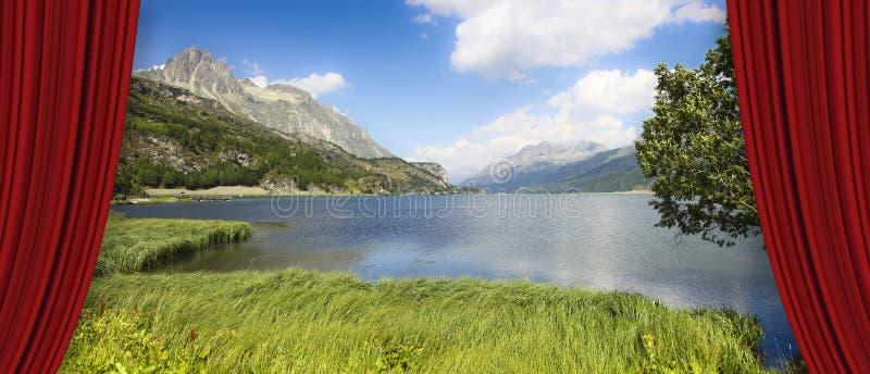 Cortinas vermelhas do teatro aberto contra o lago Sils no vale superior de Engadine em um dia de verão Europa - Suíça - imagem do fotografia de stock