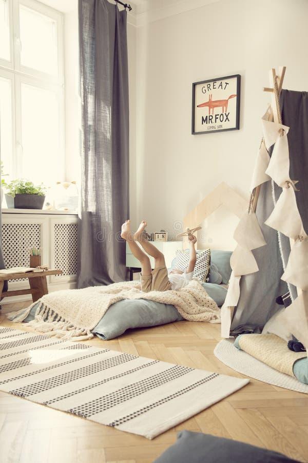 Cortinas y tienda grises en el dormitorio del muchacho acogedor con lecho azul y la alfombra modelada, foto real con la maqueta e fotografía de archivo