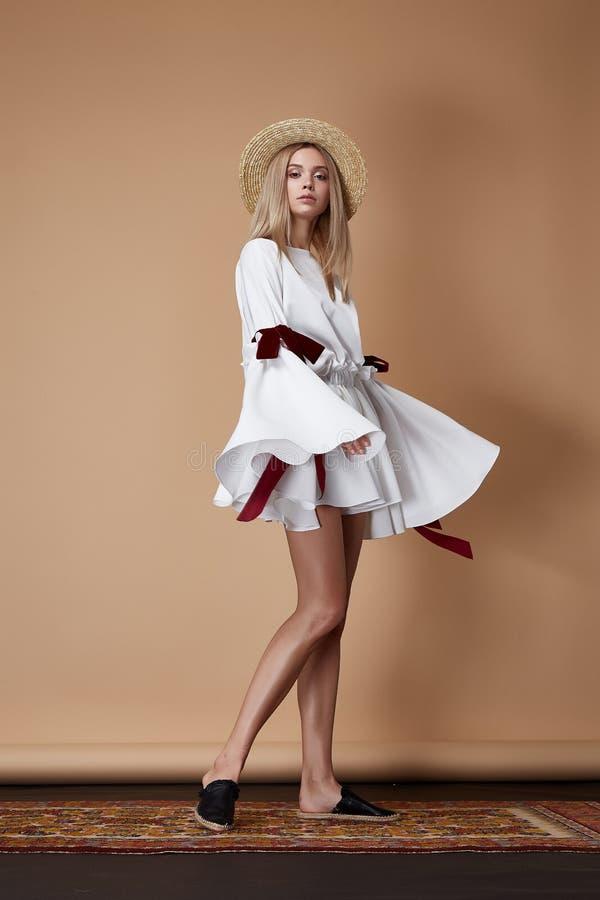 Cortocircuito rubio del sombrero de paja de la ropa de la moda del desgaste de la mujer atractiva hermosa fotografía de archivo