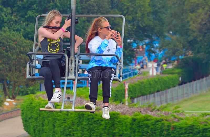 Girls taking photographs while riding on a chair lift. royalty free stock photos
