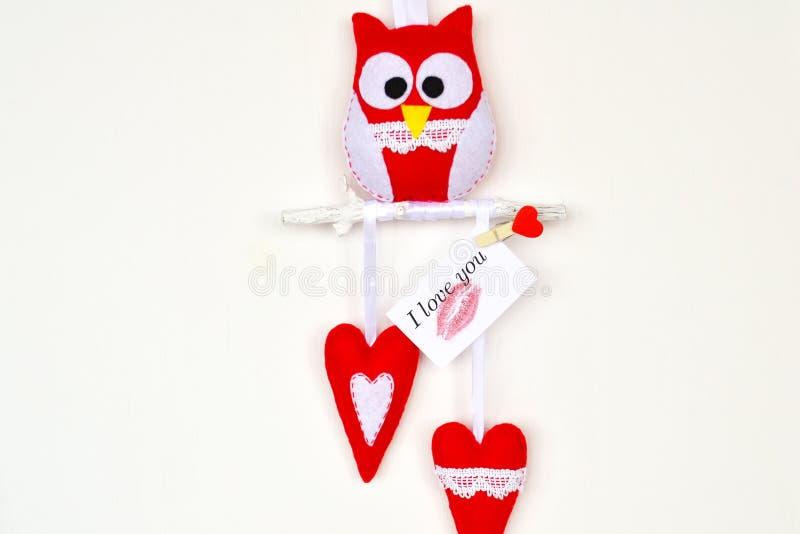 Coruja sentida vermelha e branca no ramo de madeira, 2 corações, brinquedos feitos a mão imagens de stock royalty free
