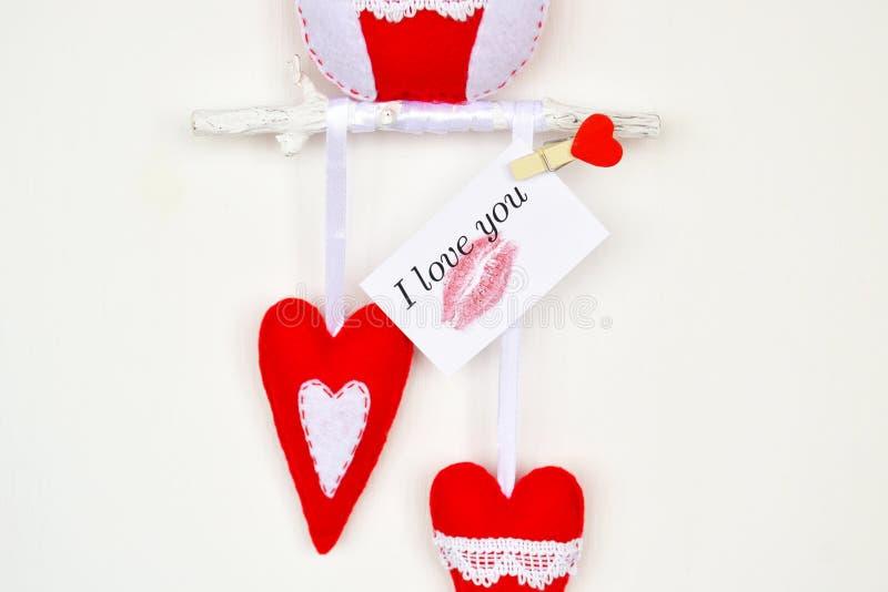 Coruja sentida vermelha e branca no ramo de madeira, 2 corações, decoração feito a mão fotografia de stock royalty free