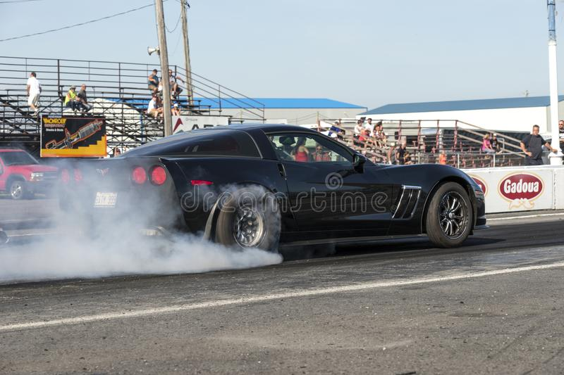 Corvette smoke show. Rear side view of Chevrolet corvette making a smoke show at the starting line on the track during the john scotti all out, august 20 2016 stock images