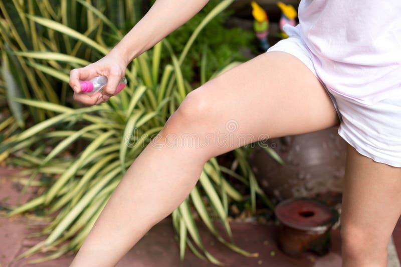 Cosa repellente di insetto di spruzzatura della donna asiatica sulla sua gamba fotografia stock