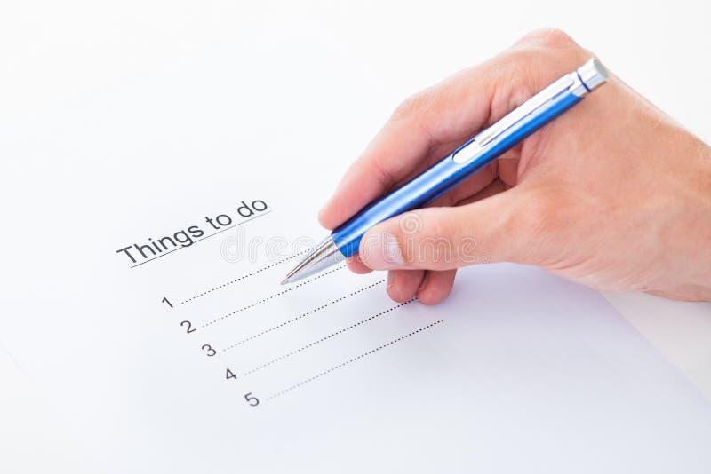 Cosas de relleno de la mano para hacer la lista foto de archivo