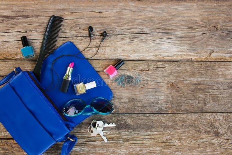 Cosas del monedero abierto de la señora Los accesorios del ` s de los cosméticos y de las mujeres cayeron del bolso azul fotos de archivo