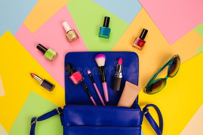 Cosas del monedero abierto de la señora Los accesorios del ` s de los cosméticos y de las mujeres cayeron del bolso azul en fondo fotografía de archivo libre de regalías