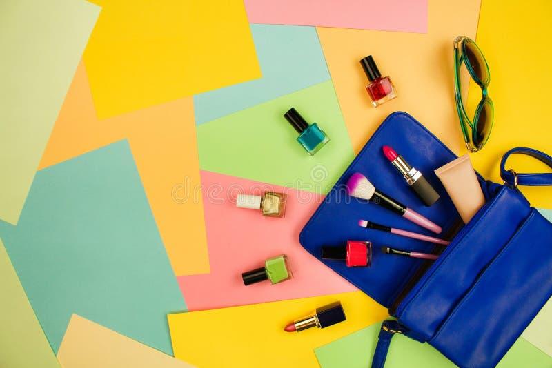 Cosas del monedero abierto de la señora Los accesorios del ` s de los cosméticos y de las mujeres cayeron del bolso azul en fondo foto de archivo