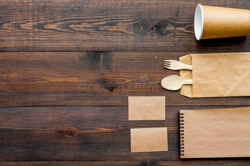 Cosas disponibles Bolsa de papel, vajilla, cuaderno en espacio de madera de la copia de la opinión superior del fondo fotos de archivo