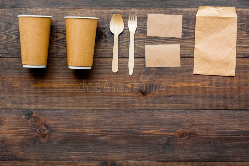 Cosas disponibles Bolsa de papel, vajilla en copyspace de madera de la opinión superior del fondo fotografía de archivo