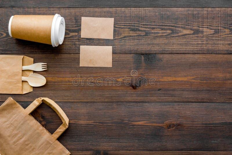 Cosas disponibles Bolsa de papel, vajilla en copyspace de madera de la opinión superior del fondo imagenes de archivo
