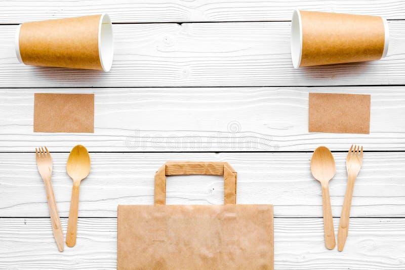 Cosas disponibles Bolsa de papel, vajilla y cuaderno en el copyspace de madera blanco de la opinión superior del fondo fotografía de archivo