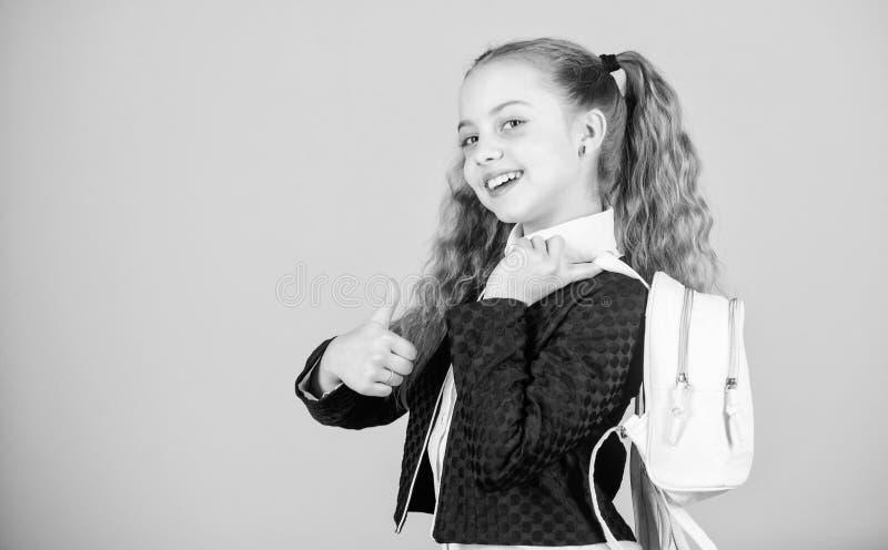 Cosas que llevan en mochila Aprenda c?mo mochila apta correctamente El peque?o cutie de moda de la muchacha lleva la mochila popu foto de archivo libre de regalías