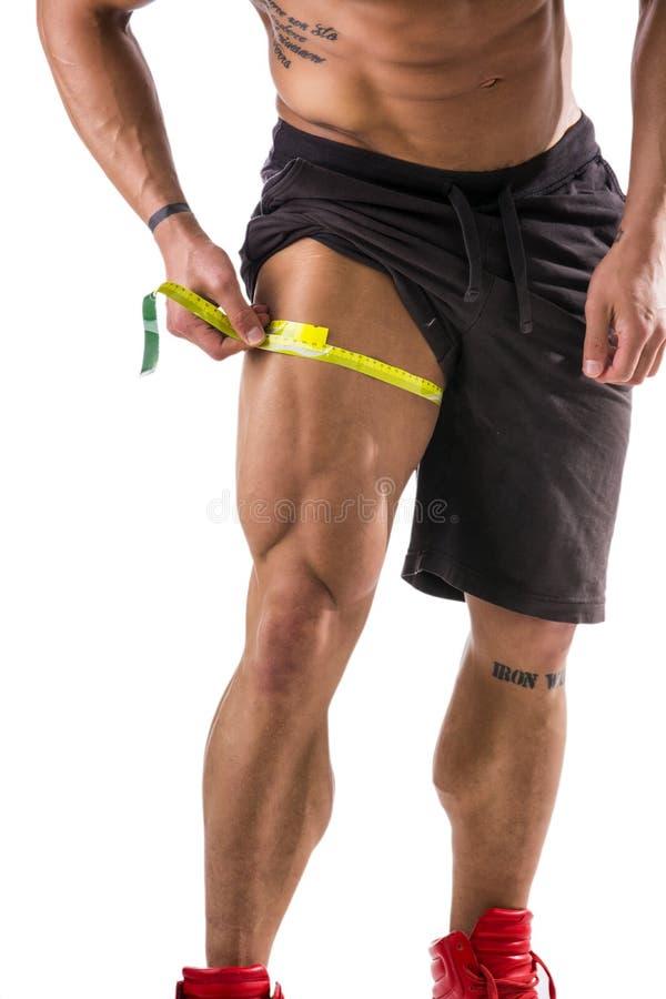 Coscia di misurazione dell'uomo muscolare del culturista con la misura di nastro fotografia stock