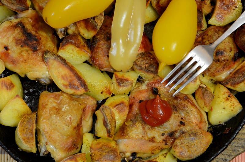 Coscie del pollo fritto con le patate con l'aggiunta dei pomodori e dei peperoni inscatolati fotografie stock libere da diritti