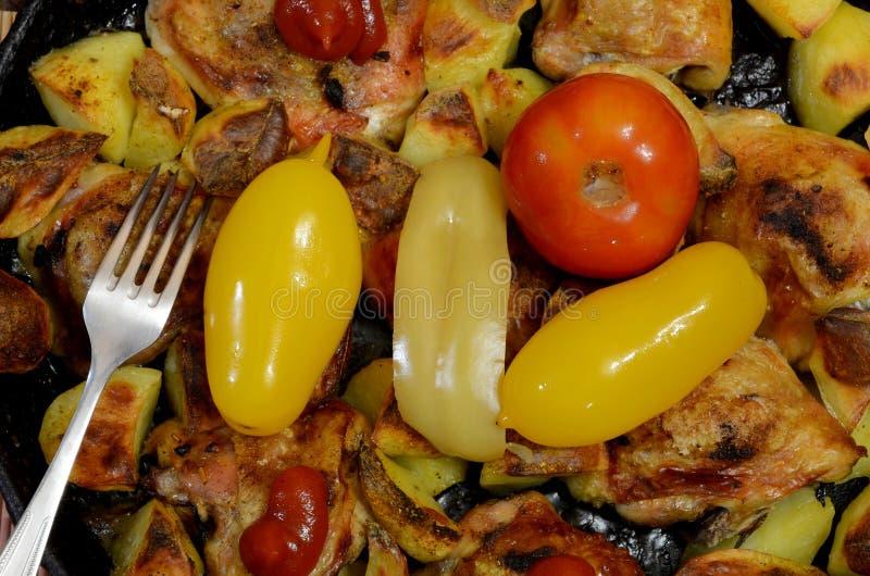 Coscie del pollo fritto con le patate con l'aggiunta dei pomodori e dei peperoni inscatolati immagini stock