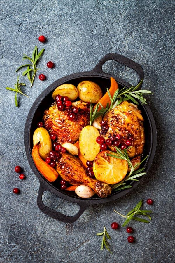 Coscie di pollo arrostite con gli ortaggi a radici, il limone, l'aglio, il mirtillo rosso ed i rosmarini sulla pentola immagini stock
