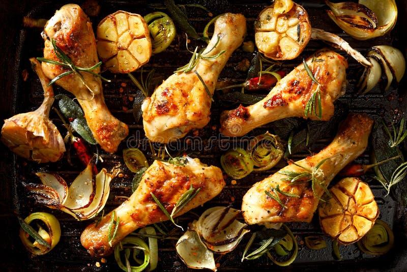 Coscie di pollo arrostite con l'aggiunta dei rosmarini, dell'aglio, della cipolla, del porro e delle spezie aromatici su un piatt fotografia stock libera da diritti