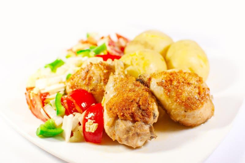 Coscie di pollo arrostite con la patata e le verdure fotografia stock