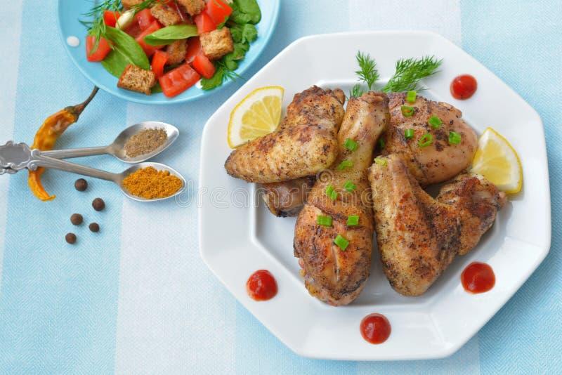 Coscie di pollo ed ali croccanti con il limone, salsa al pomodoro sul piatto bianco fotografia stock