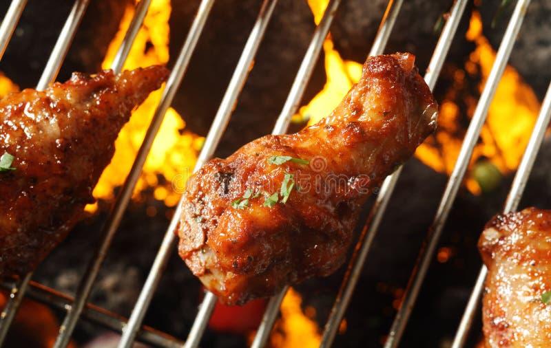 Coscie di pollo marroni croccanti su un barbecue immagine stock
