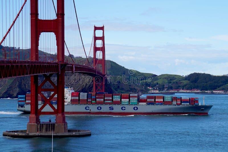 Cosco cargo ship passes beneath the Golden Gate bridge in San Fransisco stock image