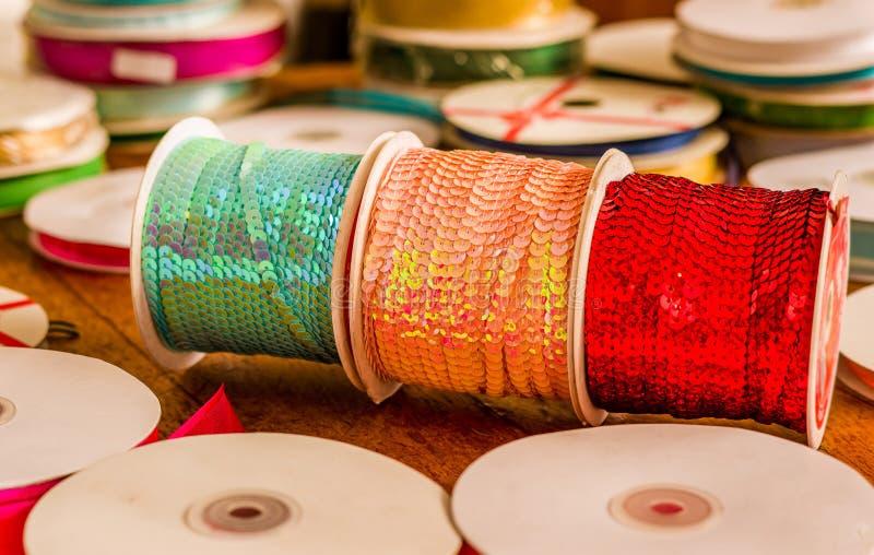 Cose para arriba de los rollos brillantes de lentejuelas coloridas se pone verde, rosa y papeleo, multicolores sobre una tabla de fotografía de archivo libre de regalías