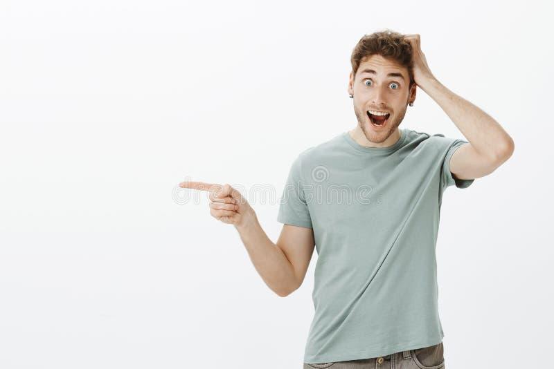 Cose stupefacenti vedenti sorprese e felici di sensibilità attraente impressionata del giovane, tenendo mano sulla testa e gridan fotografia stock