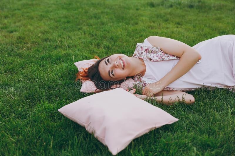 Cose up portrait of smiling happy joyful beautiful woman in light dress lying on pink pillow on green grass lawn in city royalty free stock photo