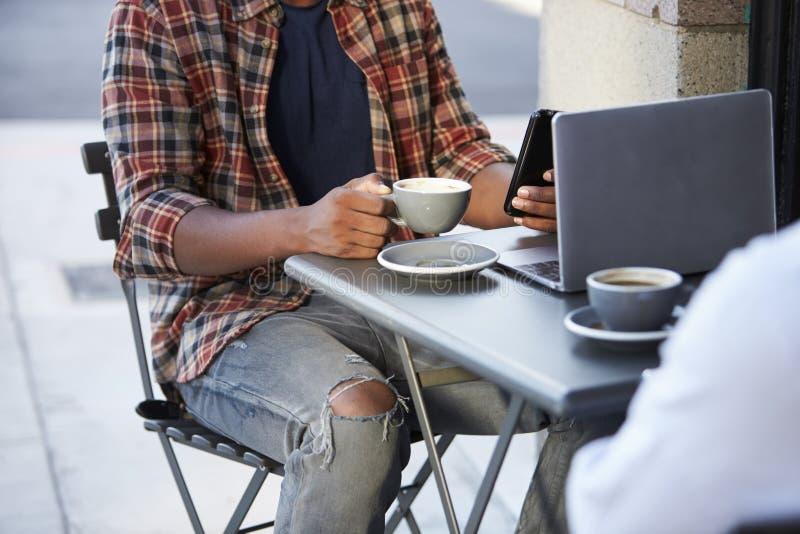 Cosecha baja de la sección de dos hombres adultos que se sientan fuera de un café fotografía de archivo