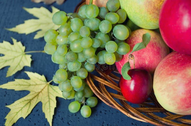Cosecha de frutas maduras - las manzanas, uvas, ciruelos, peras en placa de madera grande en fondo negro, adornaron las hojas de  fotos de archivo
