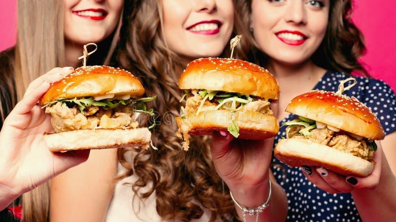Cosecha de los amigos que sostienen las hamburguesas deliciosas con el pollo y las verduras fotografía de archivo libre de regalías