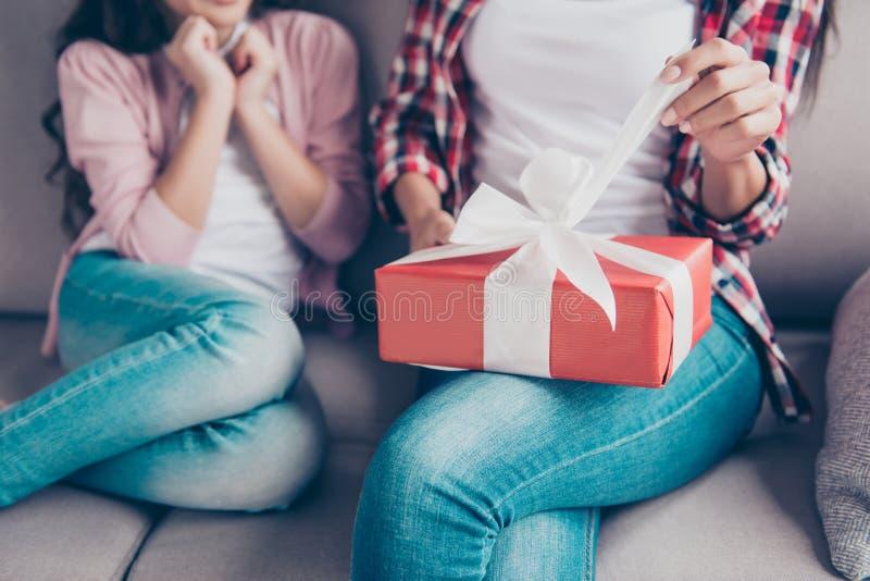 Cosechado cerca encima de la foto del ` s de la mujer da el desempaque de la caja de regalo roja o foto de archivo libre de regalías