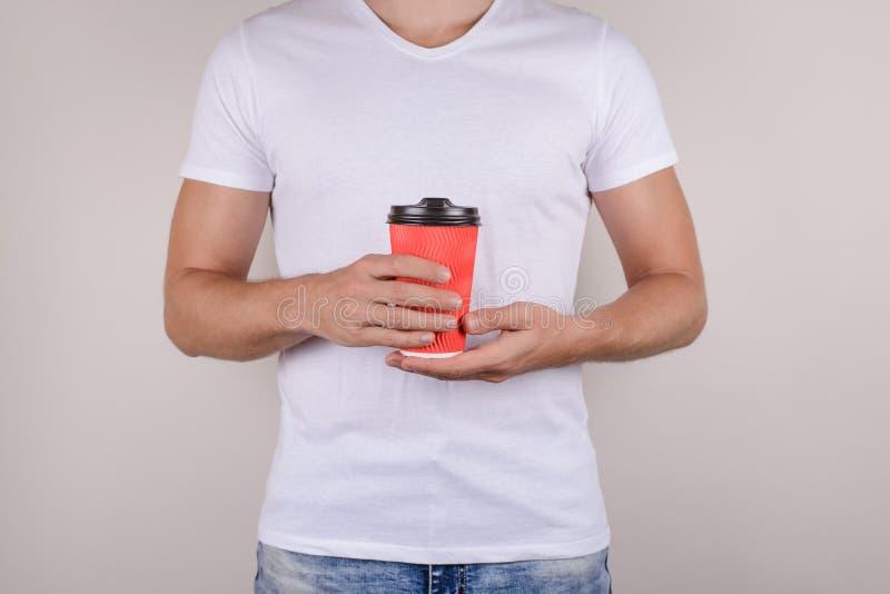 Cosechado cerca encima de la foto de la taza roja viva brillante con la tapa plástica del marrón del casquillo en manos del hombr imagen de archivo libre de regalías