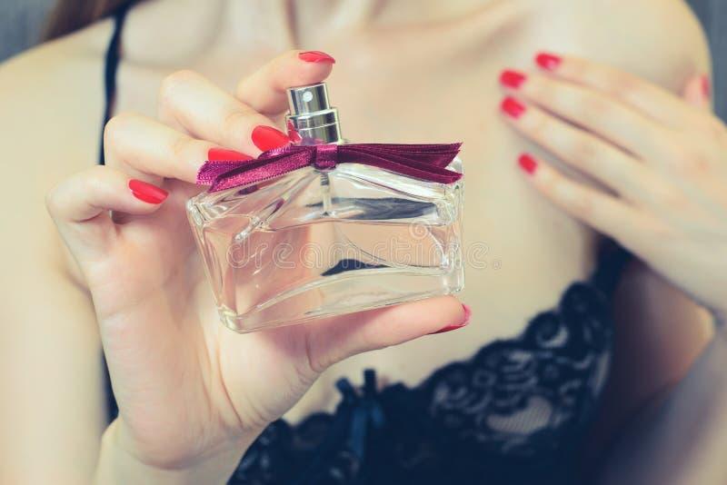 Cosechado cerca encima del retrato de la muchacha hermosa Mujer en la ropa atractiva que aplica perfume en su cuello Fasionable d foto de archivo