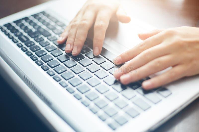 Cosechado cerca encima del tiro del ` s de la mujer da mecanografiar en el teclado mientras que charla usando el ordenador portát fotos de archivo libres de regalías