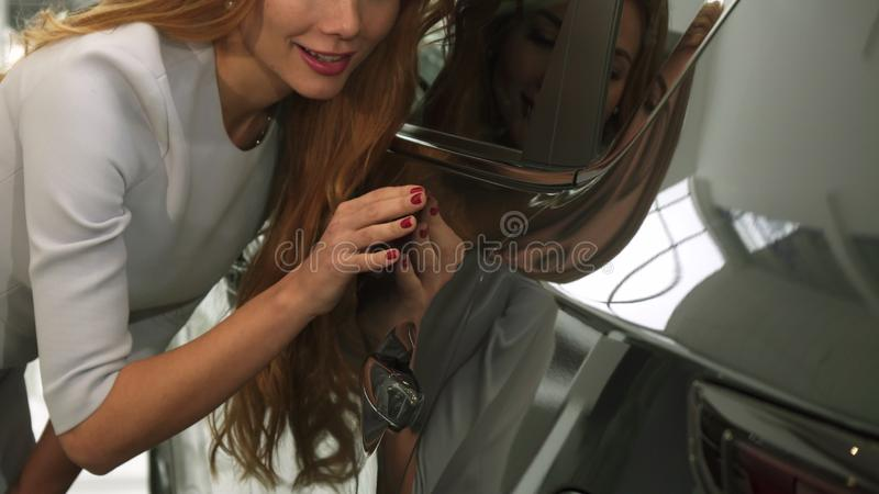 Cosechado cerca para arriba de una mujer que comprueba hacia fuera la pintura del coche en un nuevo automóvil en la representació fotos de archivo