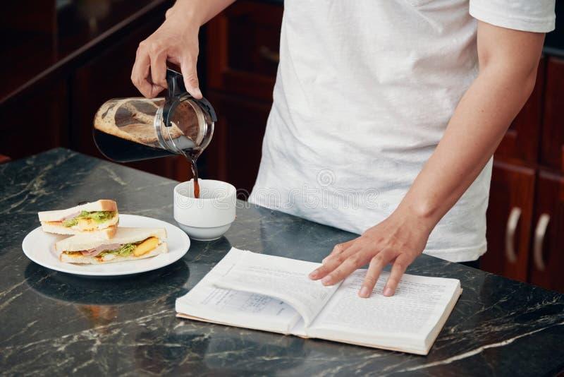 Coseche al hombre con el café de colada del libro para el desayuno fotografía de archivo libre de regalías