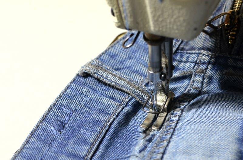 Cosiendo, agujero de costura en tejanos con una máquina de coser Parte del primer de la máquina de coser y del paño de los vaquer fotografía de archivo